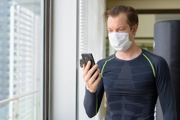 Giovane con maschera utilizzando il telefono e pronto per l'esercizio durante il covid-19