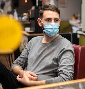 Giovane con mascherina medica presso il negozio di barbiere
