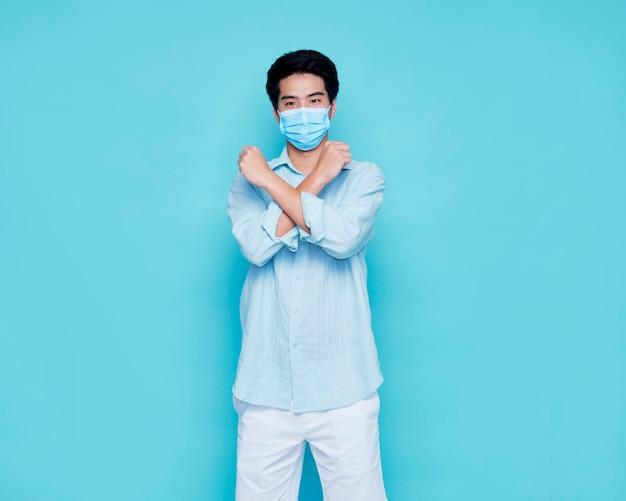 Giovane con mascherina medica sulla parete blu, spazio per il testo. protezione dal virus