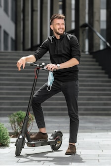 Giovane con mascherina medica su scooter elettrico