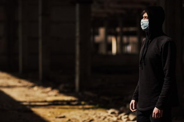 Giovane uomo con maschera medica in piedi in edifici abbandonati nella giornata di sole.
