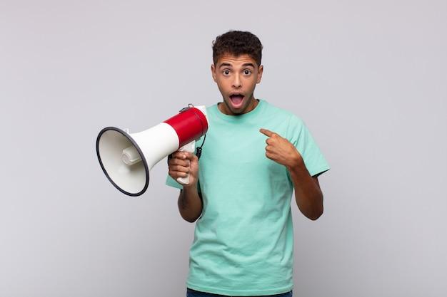 Giovane con un megafono che si sente felice, sorpreso e orgoglioso, indicando se stesso con uno sguardo eccitato e stupito