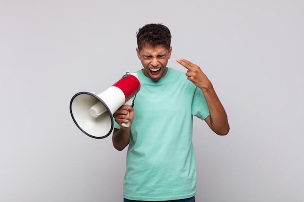Giovane con un megafono che sembra infelice e stressato, gesto di suicidio che fa il segno della pistola con la mano, indicando la testa