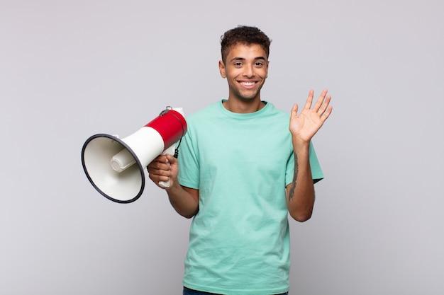 Giovane con un megafono che sorride allegramente e allegramente, agitando la mano, dandoti il benvenuto e salutandoti o salutandoti