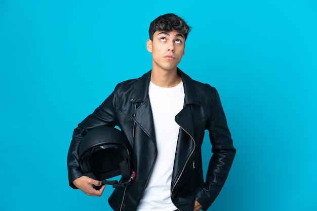 Giovane con un casco da motociclista sopra la parete blu isolata che osserva in su e con l'espressione sorpresa