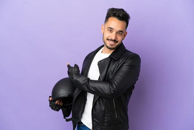Giovane con un casco da motociclista isolato su sfondo viola che punta indietro