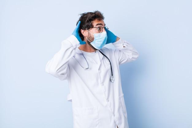 Giovane con la bocca aperta, inorridito e scioccato a causa di un terribile errore, alzando le mani alla testa. concetto di coronavirus