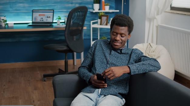 Giovane con il telefono in mano che guarda i contenuti dei servizi di streaming online, godendosi il lavoro da casa