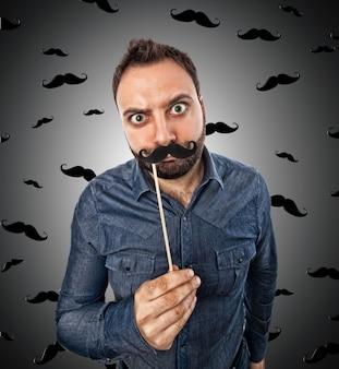 Giovane uomo con foto booth a forma di baffi