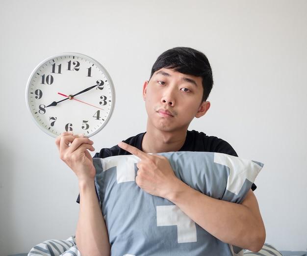 Il giovane con il cuscino punta il dito contro l'orologio in mano e si sente annoiato a lavorare in ritardo concetto