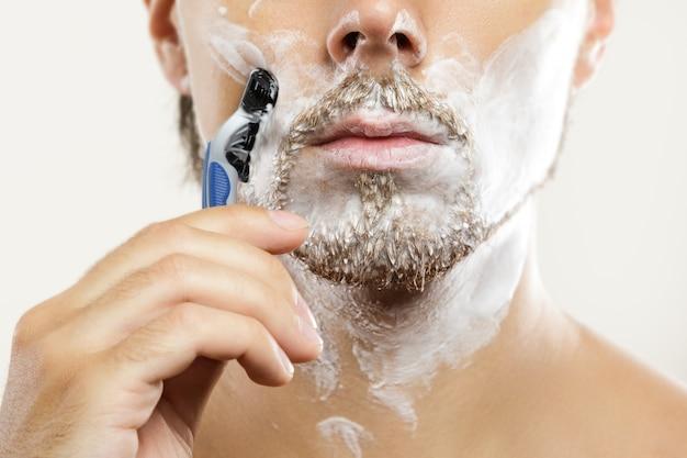 Giovane con un rasoio di sicurezza e una crema da barba sul viso