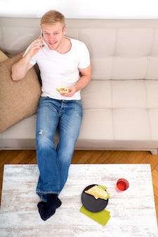 Giovane con un panino sul divano