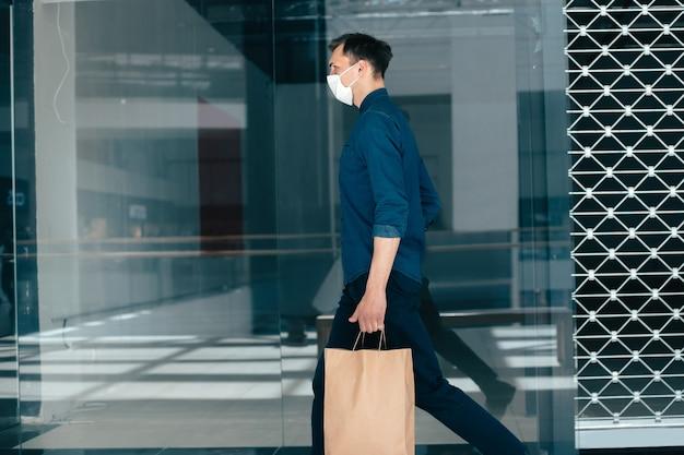 Giovane con borse della spesa a piedi lungo una strada cittadina. coronavirus in città Foto Premium