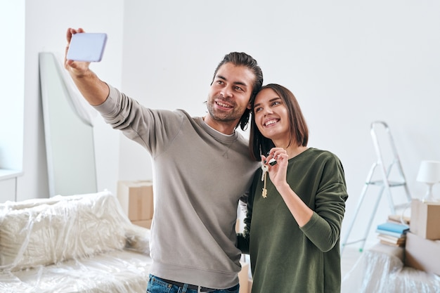 Giovane con lo smartphone che fa selfie con sua moglie felice che tiene la chiave della loro nuova casa o appartamento mentre si trovava in soggiorno