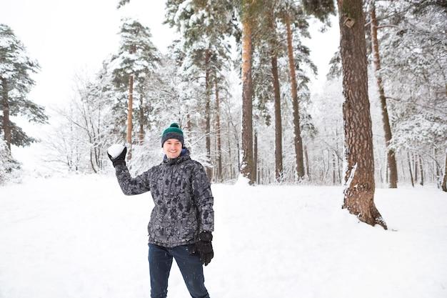 Un giovane con una palla di neve in mano si sta divertendo