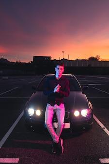 Giovane con un'auto sportiva in un parcheggio con luci colorate