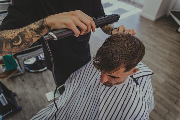 Un giovane con le braccia tatuate taglia i capelli di un uomo in un negozio di barbiere