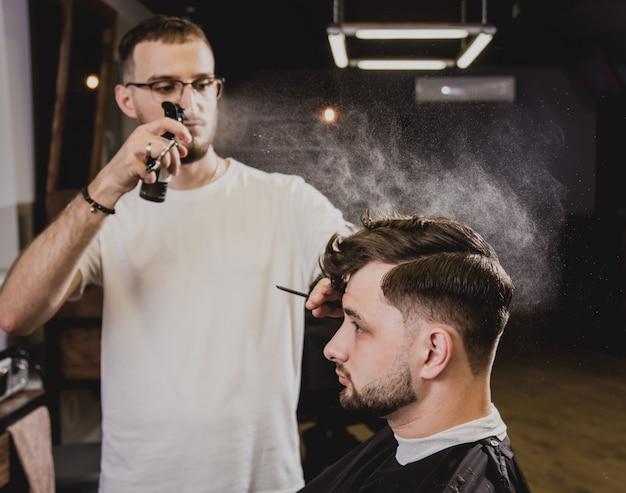 Giovane con taglio di capelli alla moda al negozio di barbiere. il barbiere fa taglio di capelli e barba.