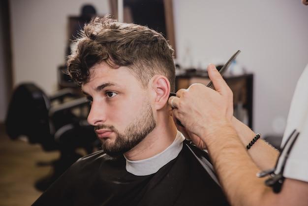 Giovane con taglio di capelli alla moda al negozio di barbiere. il barbiere fa la pettinatura e la barba.