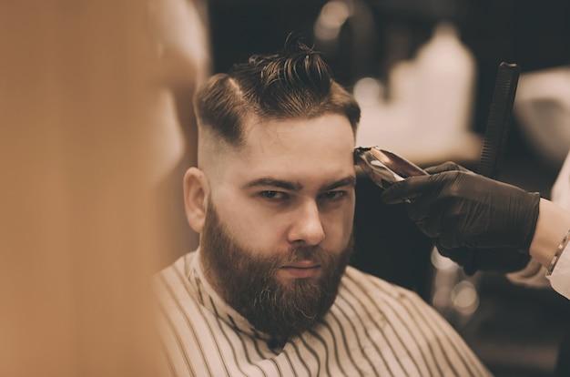 Giovane con taglio di capelli alla moda al negozio di barbiere
