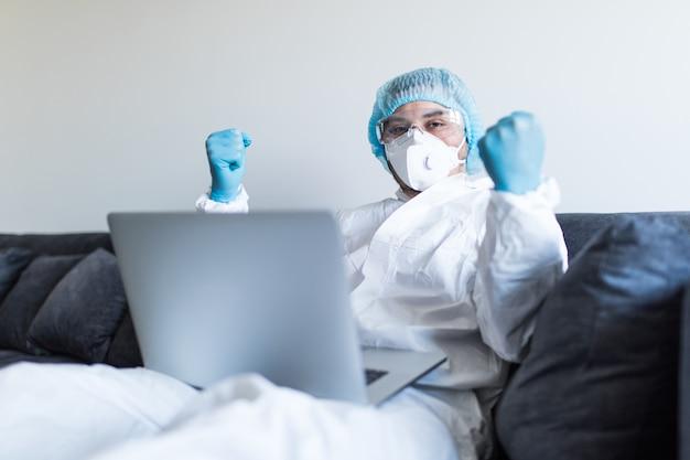 Giovane con il gesto di vittoria in vestiti di rischio biologico facendo uso del computer portatile e restando a casa all'autoisolamento