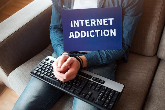 Il giovane e la donna hanno una dipendenza dai social media. dipendenza da laptop o smartphone. ostaggio dei social media. catene intorno al polso. dipendenza da internet.