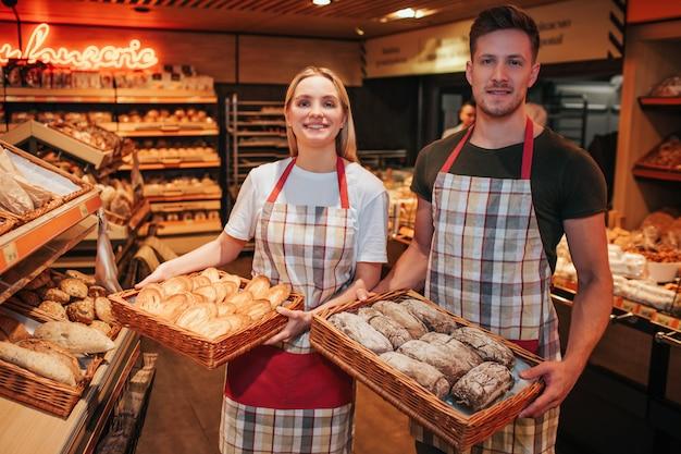 Cestini della tenuta della donna e del giovane di pane saporito fresco in mani