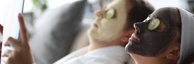 Giovane uomo e donna sdraiati sul divano con maschere idratanti