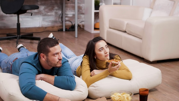Giovane uomo e donna sdraiati sul pavimento guardando la tv e mangiando pizza con la schiena sullo sfondo.