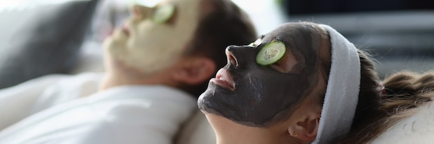 Giovane uomo e donna sdraiati con maschere cosmetiche sul viso e fette di cetriolo sugli occhi