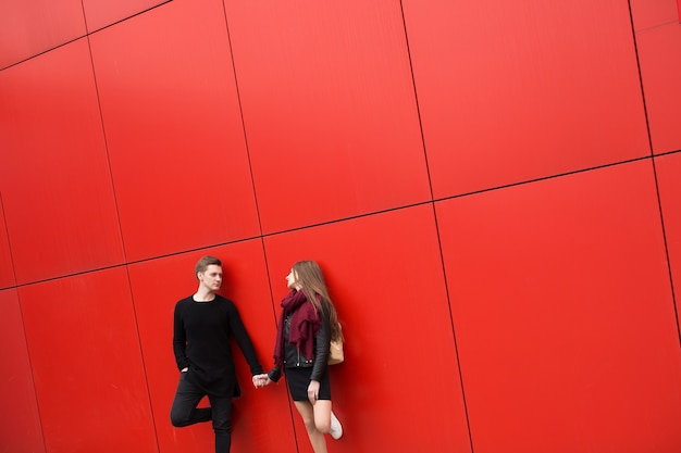 Giovane uomo e donna in passione, emozione, per strada con lo sfondo del muro rosso. moda