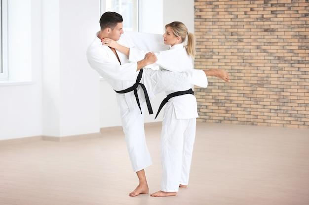 Giovane uomo e donna che praticano karate nel dojo