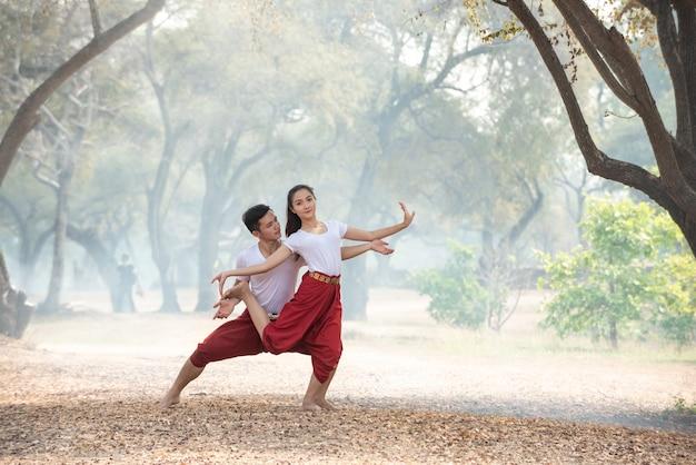 Giovane uomo e donna che praticano una danza tradizionale thailandese