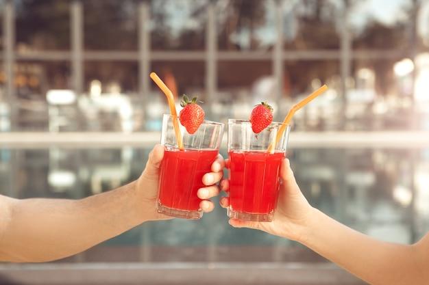 Il giovane e la donna riposano insieme vicino alla piscina bevendo cocktail