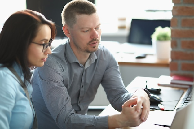 Giovane uomo e donna seduti alla scrivania in ufficio