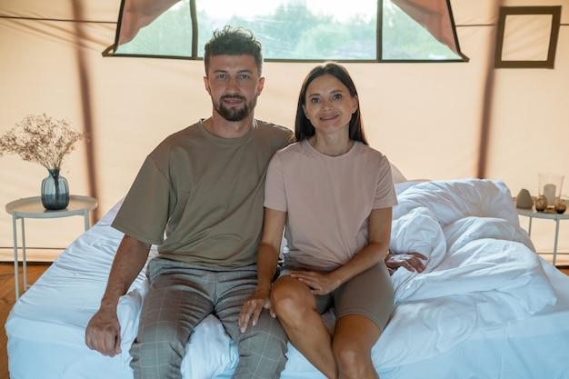 Giovane uomo e donna seduti sul letto disfatto al mattino