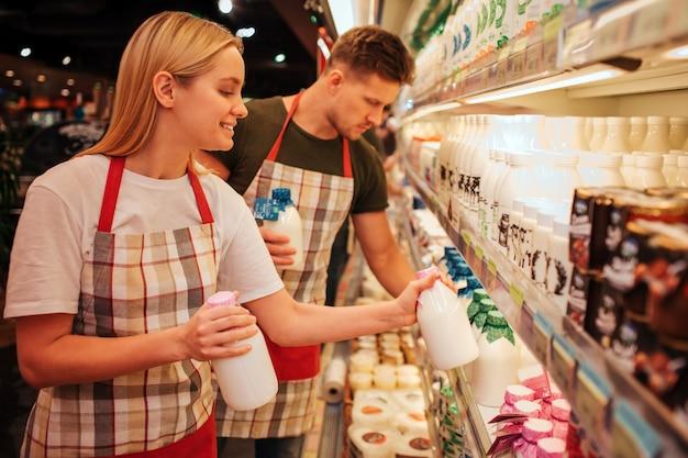Giovane uomo e donna stanno in drogheria e scaffale di prodotti lattiero-caseari.