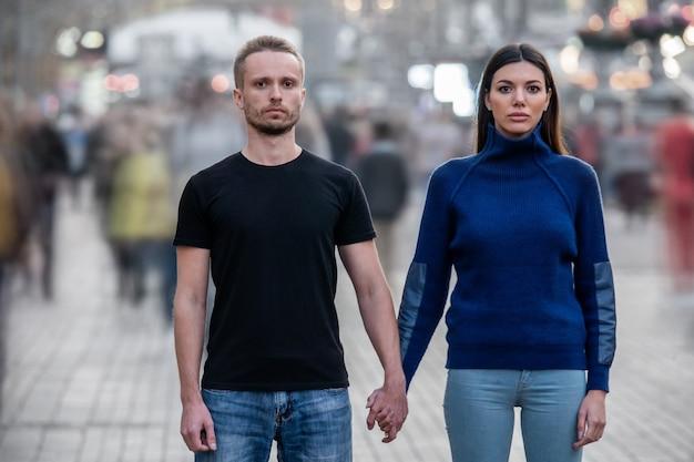 Il giovane e la donna stanno in mezzo alla strada e si tengono per mano