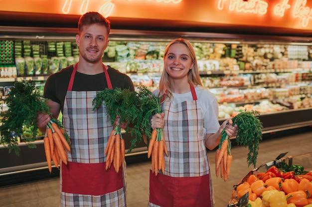 Giovane uomo e donna stanno al cesto di verdure nel negozio di alimentari.