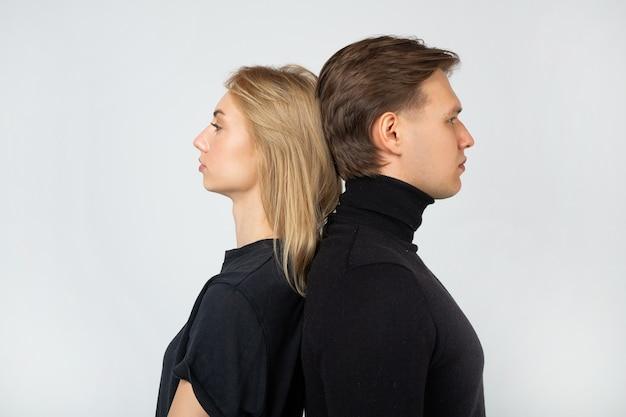 Giovane uomo e donna in piedi schiena contro schiena