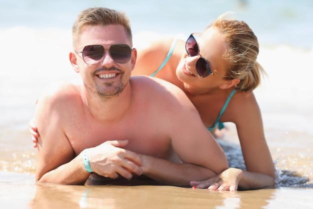 Giovane uomo e donna in occhiali da sole sdraiato sulla riva del mare