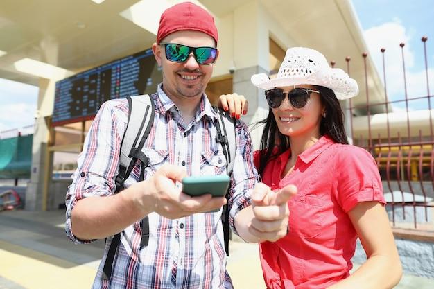 Giovane uomo e donna in occhiali da sole in piedi sul binario del treno e guardando lo schermo del cellulare