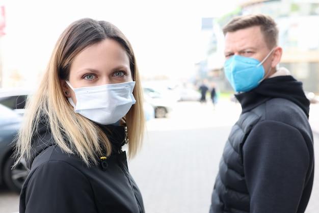 Giovane uomo e donna che camminano per strada indossando maschere protettive