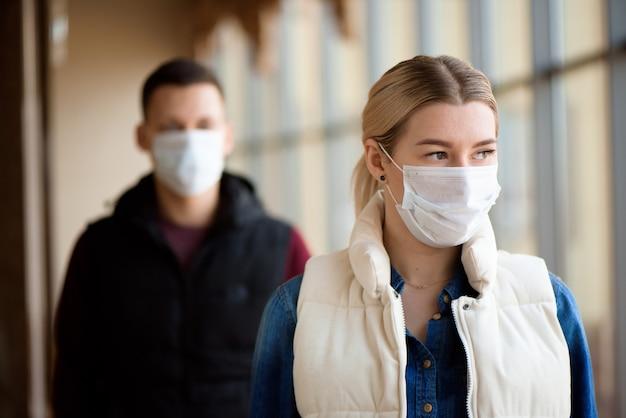 Giovane uomo e donna che indossa maschere mediche in una lounge dell'aeroporto