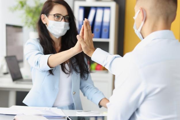 Giovane e donna che indossano maschere mediche protettive che danno cinque dietro il tavolo in ufficio