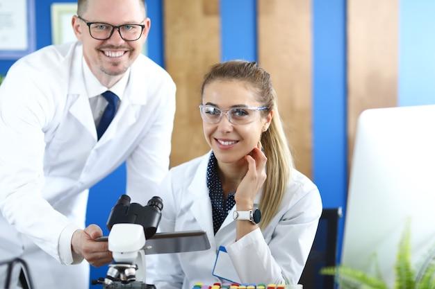 Giovane uomo e donna in uniforme bianca seduti dietro il tavolo con il microscopio