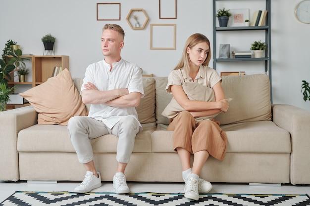 Giovane uomo e donna con le braccia incrociate sul petto seduti sul divano in soggiorno dopo una discussione ed esprimendo tristezza e offesa