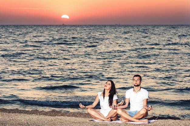 Il giovane e la donna fanno yoga e meditano sulla spiaggia all'alba. concetto di stile di vita sano.