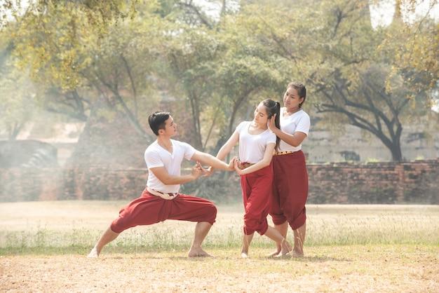 Giovani e donne che praticano una danza tradizionale thailandese