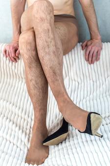 Giovane in collant di nylon da donna e scarpe con i tacchi. transessualità. lgbt